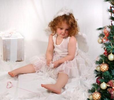 Ангел возле ёлки сидит ноги в стороны