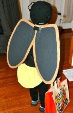 Ребенок в костюме жука с крыльями из бумаги