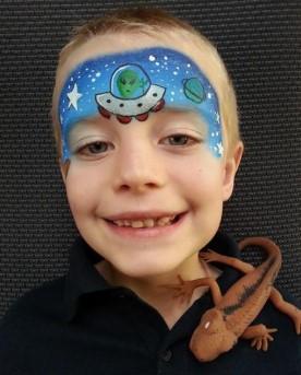 Рисунок летающей тарелки в звездном небе на лбу у мальчика