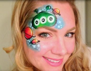 Рисунок планет и головы зеленого инопланетянина на лице