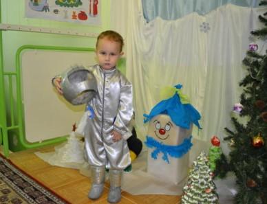 Костюм космонавта серебристый на ребенке возле новогодней елки