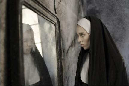 монахиня смотрит в зеркало