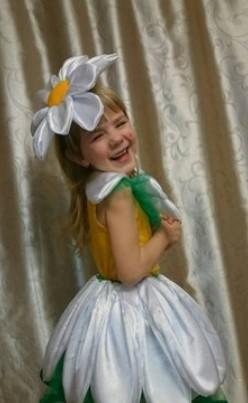 Смеющаяся девочка в костюме ромашки