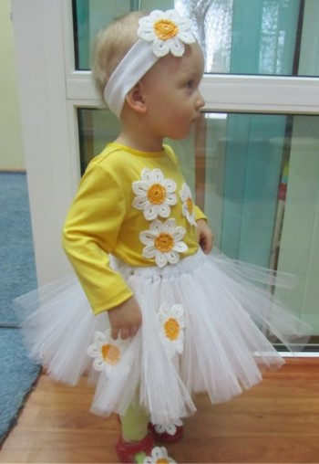 Костюм ромашки с декоративными цветами из кофты с длинными рукавами, пышной белой юбки и повязки на голову на маленькой девочке