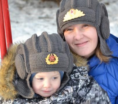 Вязанные шлемы танкиста со значками на женщине и ребенке