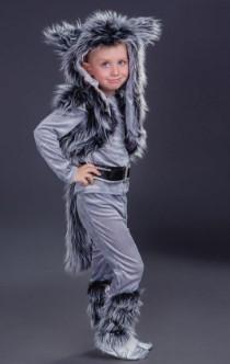 Волк в меховой накидке, с хвостом и лапами на сером фоне в полный рост