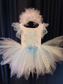 Белое платье с пышной юбкой на фоне синей шторы